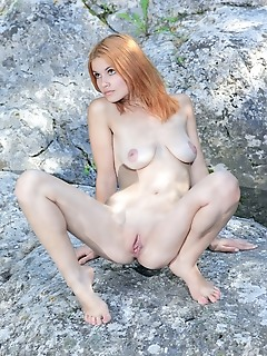 Violla a redhead violla a poses on the big rock as she flaunts her naked, creamy body.
