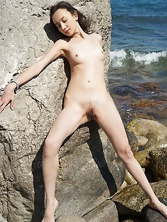 Djessy djessy flaunts her unshaven pussy as she poses on the rocky beach.