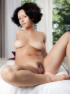 Pammie lee pammie lee shows off her curvy body with large breasts as she sensually poses on the bed.