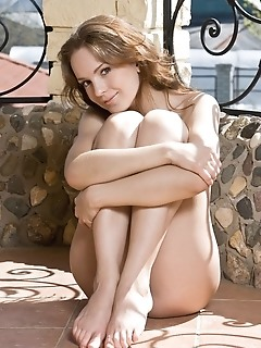 Naughty but cute babe in a daring veranda striptease.