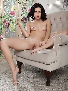 Mona mona bares her slender body with pink nipples and small pussy on the chair.