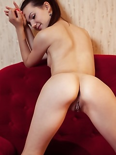 Iva alluring iva strips on the red couch baring her shaved pussy.