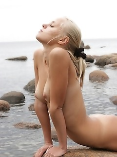 Outdoor-loving cutie, bare, open and uninhibited among the rocky coast.