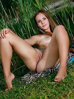 Hailey new model hailey bares her slender, tanned body on the grass.