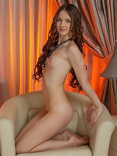 Cherish with a shy smile, cherish poses on the cream-colored couch, showing off her pink, puffy tits, slender waist, smooth, round ass, and long, svel