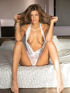 Melena a top model melena a strisp her sexy, white lingerie on the bed.