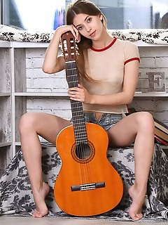 Avery avery displays her sexy, slender body as she poses with her guitar.