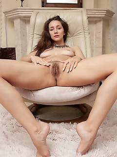 Megan muse megan muse displays her petite, naked body and hairy pussy on the chair.