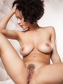 Pammie lee curly-haired pammie lee shows off her big tits and trimmed pussy on the bed.