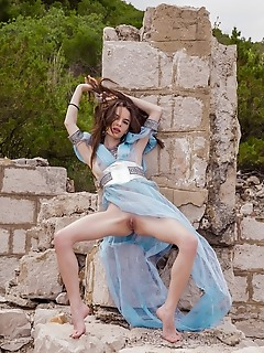 Debora a wearing a diaphanous dress, debora a poses seductively against a stone wall